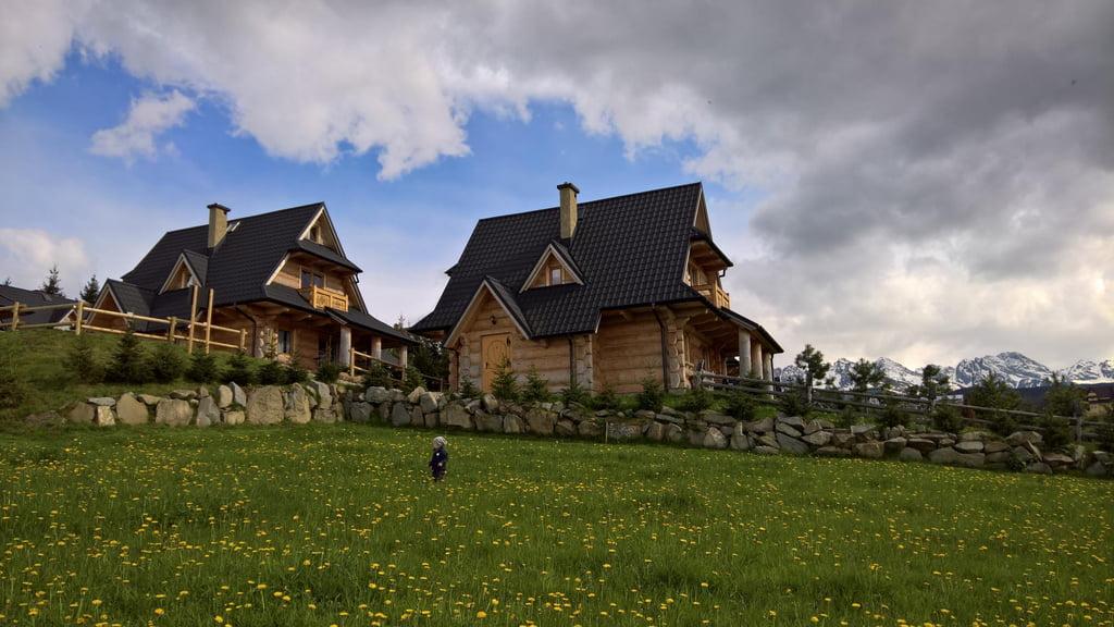 dwa góralskie domy stoją na wzgórzu, w oddali widoczne są góry