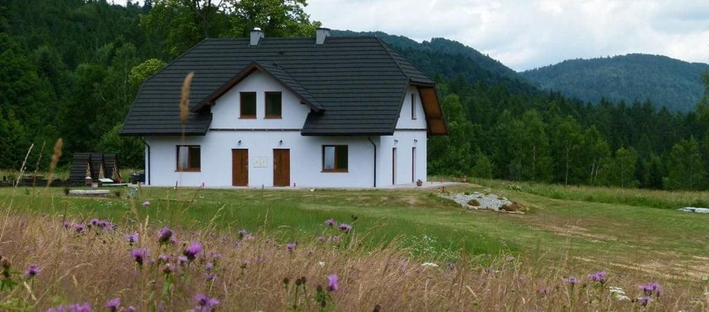biały dom stojący na polanie pod lasem