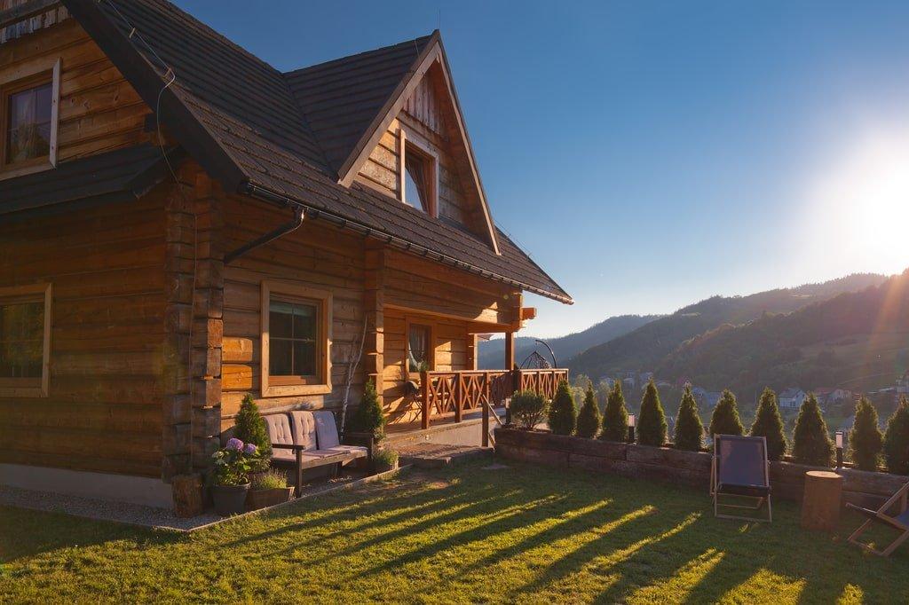 drewniana chata na wzgórzu, w tle góry