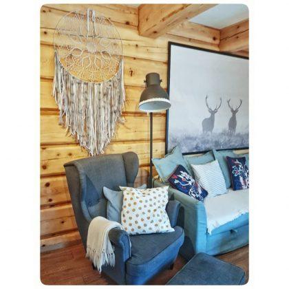 niebieski, wysoki fotel, niebieska kanapa a na nich poduchy, łapacz snów na ścianie