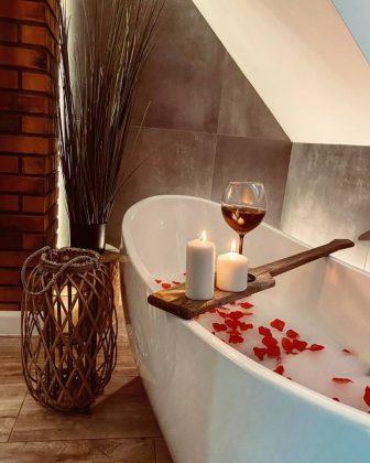 wanna, lampka czerwonego wina, płatki róż w wodzie, zapalona świeca