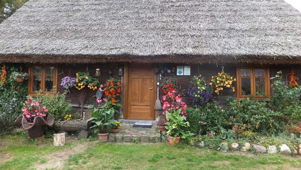 drewniana chata kryta strzechą, przed nią kwiaty - weekend nad jeziorem w Polsce