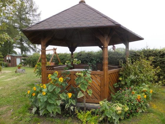 drewniana altana w ogrodzie wokół kwiaty i zieleń