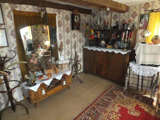 zabytkowe wyposażenie: komody, dywan, i dodatki w chacie skansenie w Borach Tucholskich
