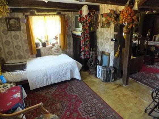 łóżko w dawnym wnętrzu w drewnianej chacie - nocleg nad jeziorem