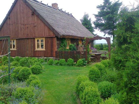 drewniana chata w otoczeniu zieleni super pomysł na nocleg w Borach Tucholskich nad jeziorem