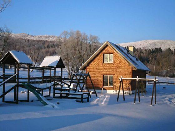 drewniany dom zasypany śniegiem, w oddali widoczne szczyty gór