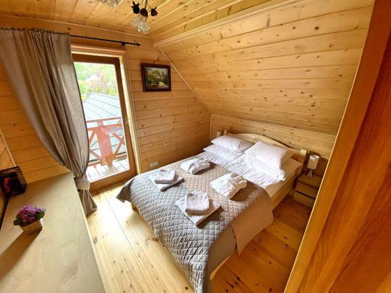 pościel na drewnianym łóżku w pokoju w którym ściany wyłożone są drewnem