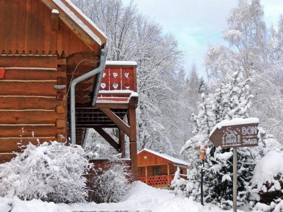 drewniana chata obsypana śniegiem