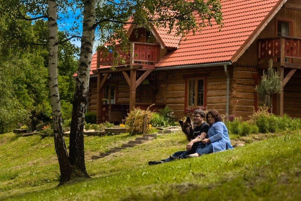 kobieta mężczyzna i pies siedzą na trawie przed drewnianym domem