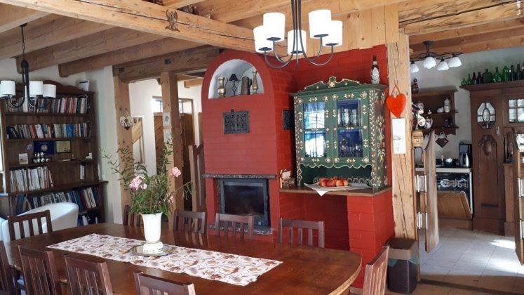 kominek, stół i krzesła w ciepłym kolorze, na ścianach i suficie drewno