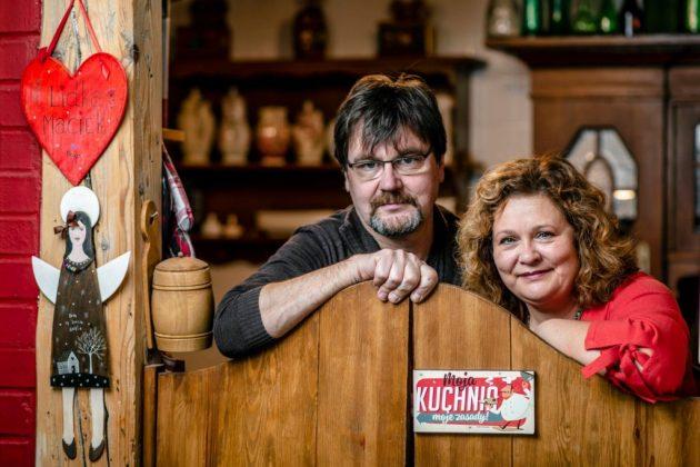 kobieta i mężczyzna opierają się o wahadłowe drzwi prowadzące do kuchni