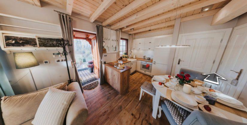 stół, kanapa i drewniane wnętrze przyjemnego salonu