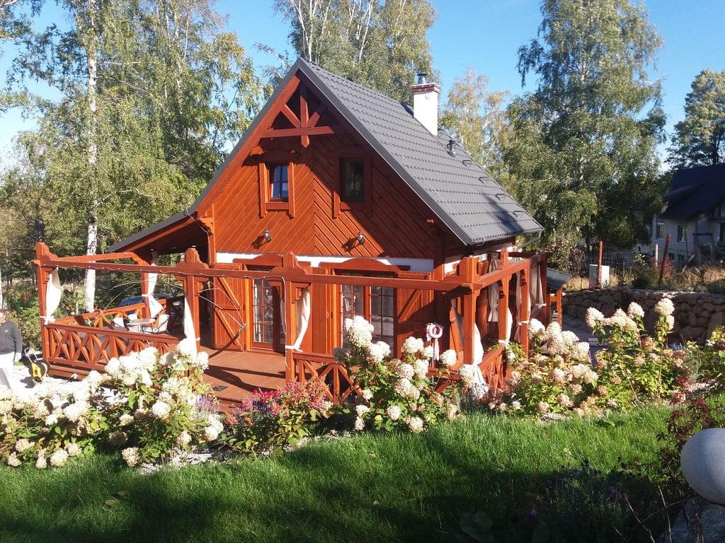 Drewniany domek wsród kwitnących kwiatów