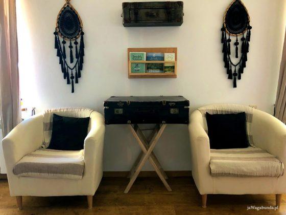 dwa fotele, stolik ze starej walizki i ozdoby na ścianach w pokoju