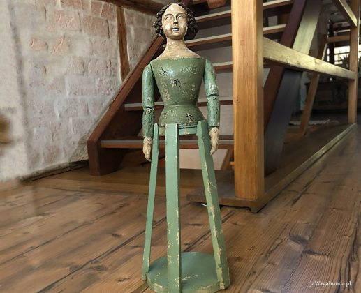 drewniana rzeźba postaci stoi na drewnianej podłodze przed schodami