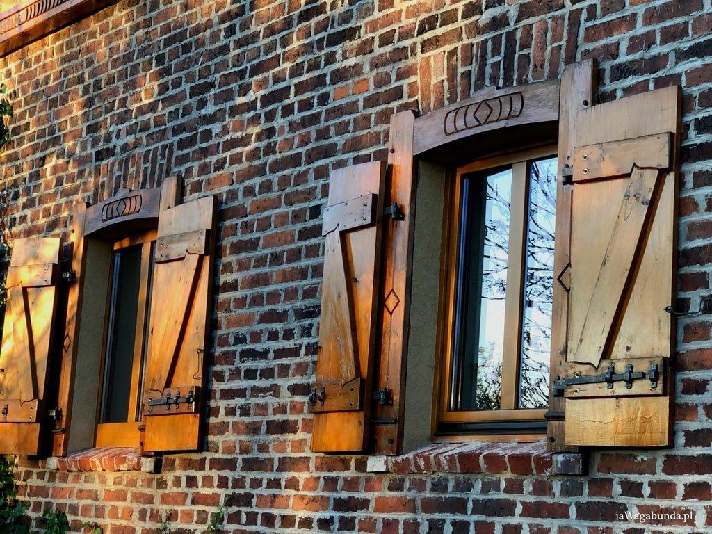 ceglany dom jego fragment z oknem i drewnianymi okiennicami