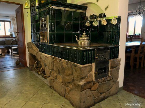 duży, stary kaflowy piec w kuchni a na nim stoi duży czajnik