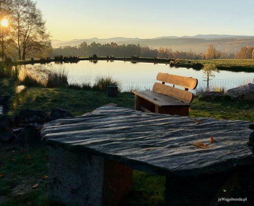 kamienny stół nad stawem z widokiem na góry i łąki