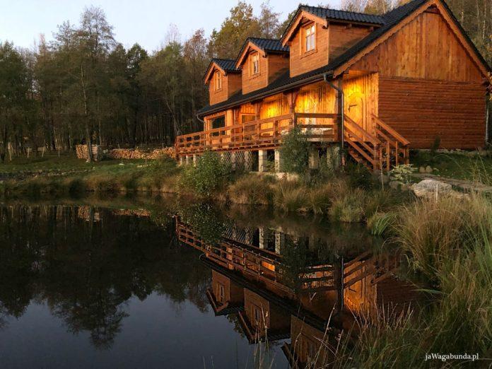 piekny drewniany dom położony nad jeziorem, oświetlony zachodzącym słońcem