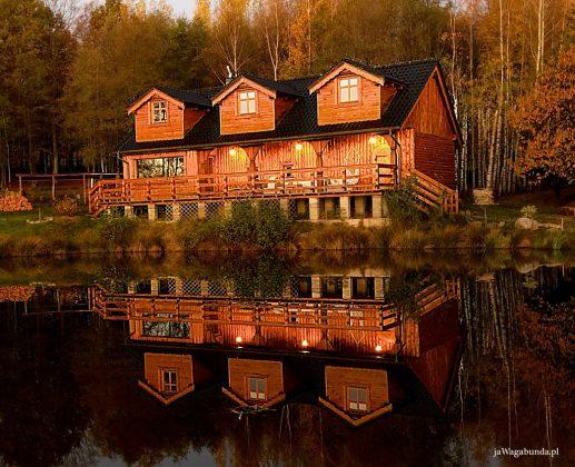 drewniany budynek odbijający się w jeziorze