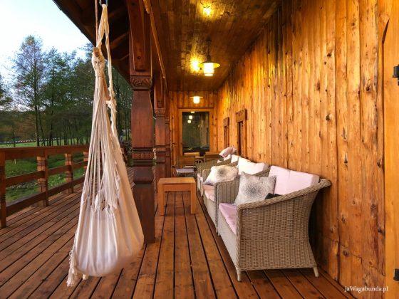 hamak na drewnianym tarasie i wiklinowe sofy z poduszkami
