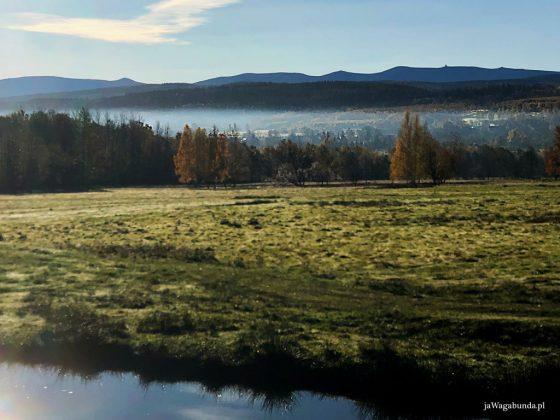 staw, łąka a na horyzoncie góry Karkonosze, a pod nimi mgły