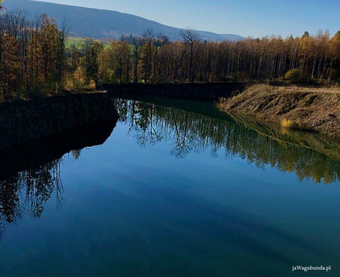 jezioro w zalanym kamieniołomie w górach izerskich, w tle widoczne Karkonosze