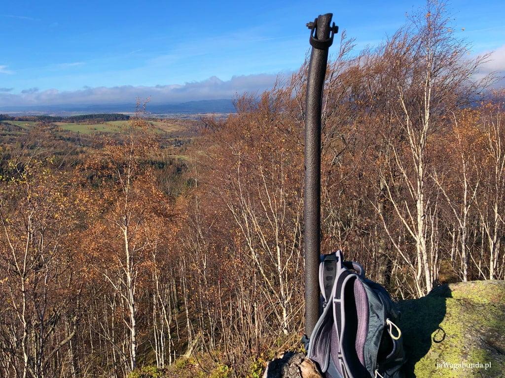 widok na góry ze skały, na skale zabezpieczenia metalowe i szary plecak górski