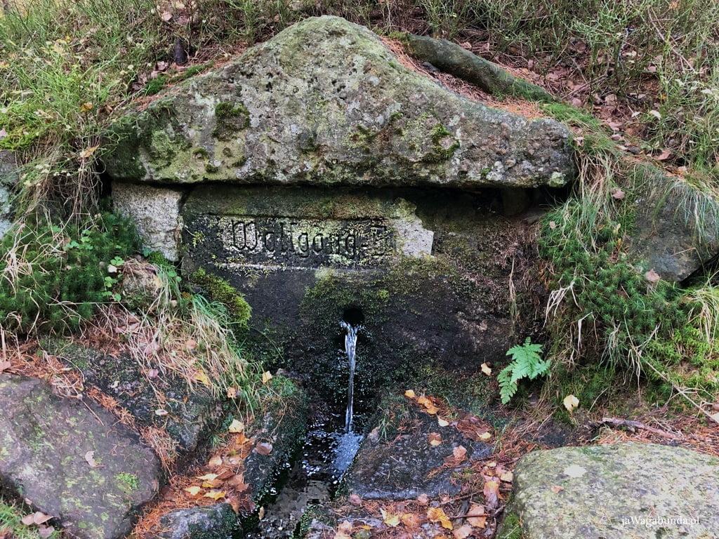 obudowane kamieniami źródło św Wolfganga z napisem wytłoczonym na kamieniu