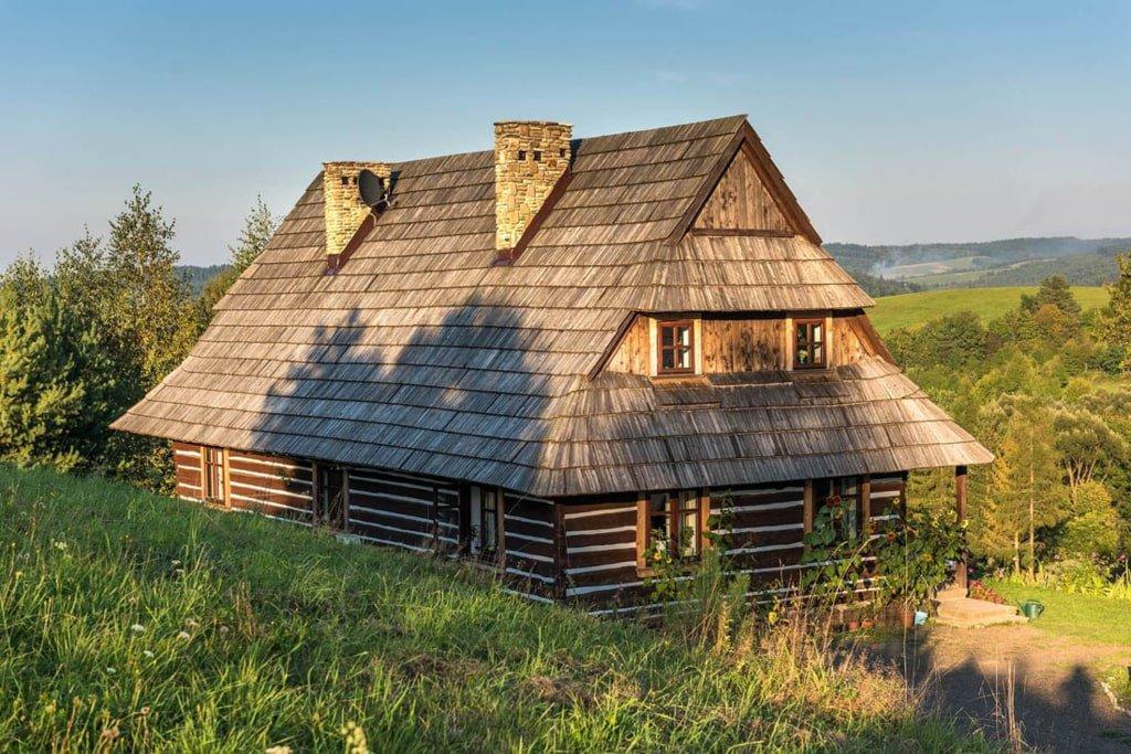 drewniana, stara chata kryta gontem wśród zieleni