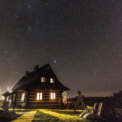 drewniana chata nocą pod rozgwieżdżonym niebiem