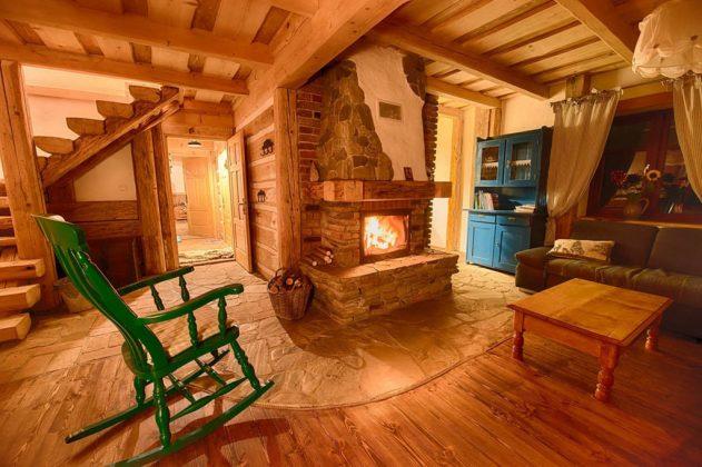 kominek, fotel bujany, drewniana podłoga i ściany