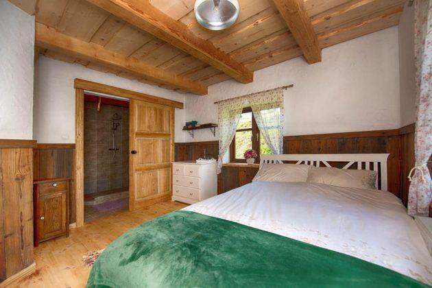 pokój z drewnianym sufitem, dużym łóżkiem i drewnianymi podłogami