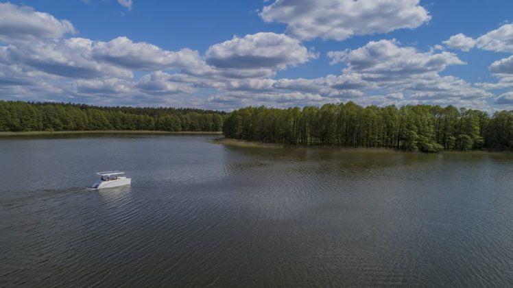 duże jezioro porośnięte trzciną a na nim katamaran