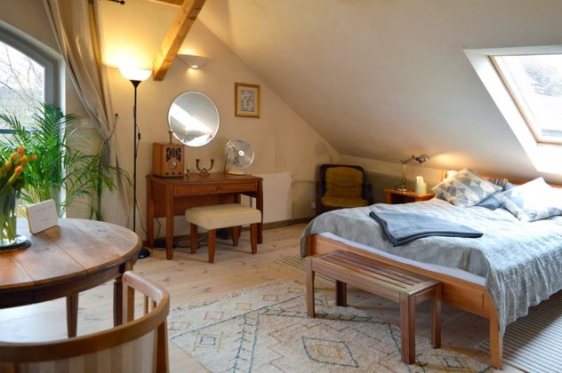 łóżko, lampa i drewniana komoda w jasnym i ładym pokoju