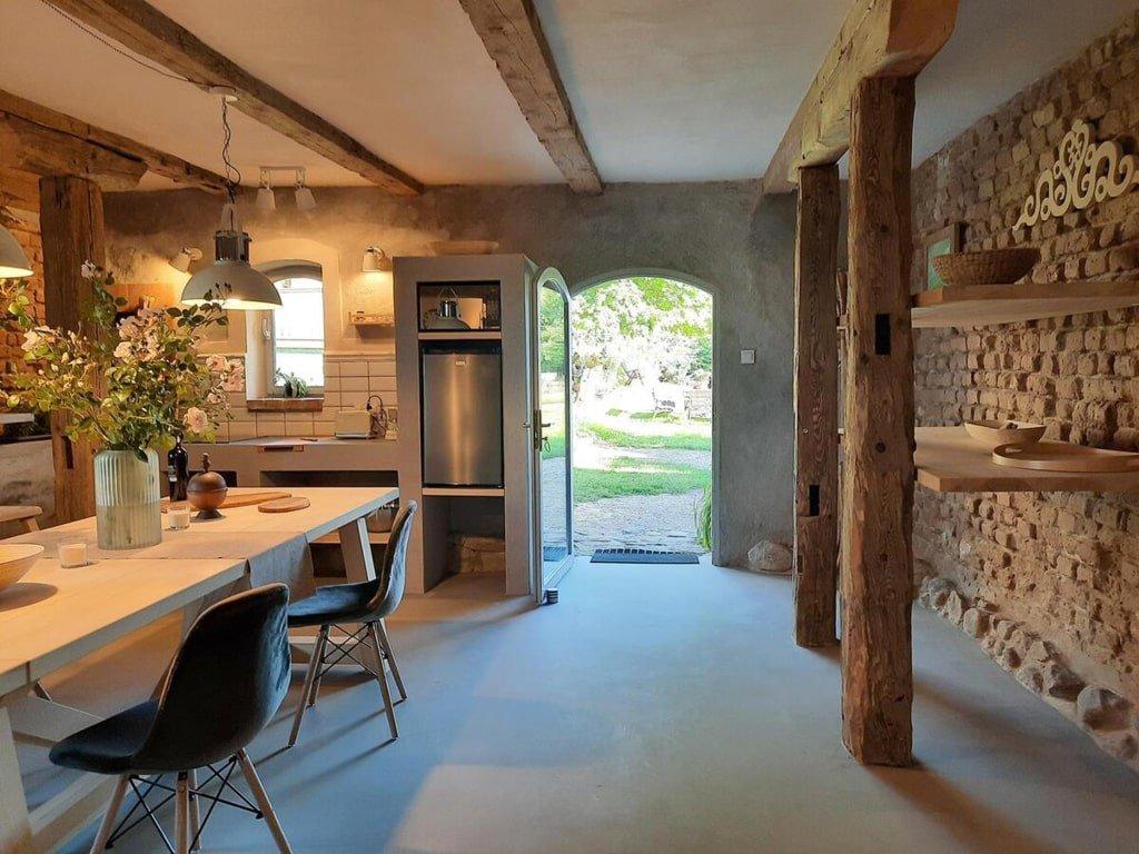 drewniane wnętrze, drewniany stół, widoczne drzwi wejściowe