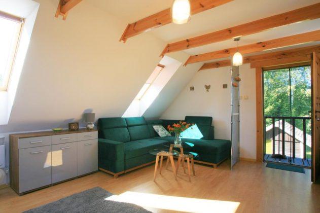 zielona kanapa w pokoju, białe ściany, belki pod sufitem