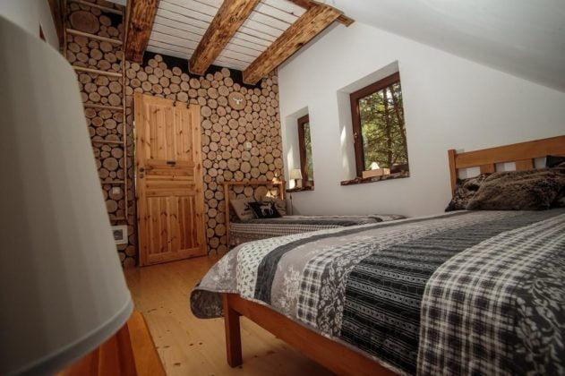 Ściana wyłożona plastrami drewna, łóżko przykryte kapą
