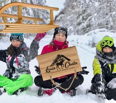 kobieta i dwójka dzieci na śniegu, sanki i tablica z napisem Chata Łosia