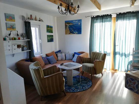 krzesła, stół, obrazy na ścianach w pokoju