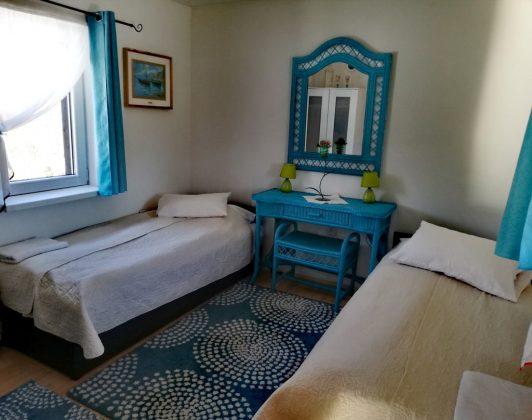 niebieska komoda pomiędzy dwoma łóżkami, nad nimi lustro na ścianie