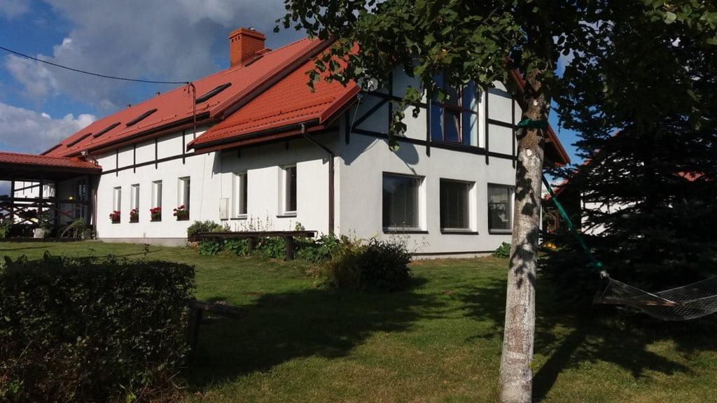 biały dom przykryty ciemną dachówką z przodu drzewo