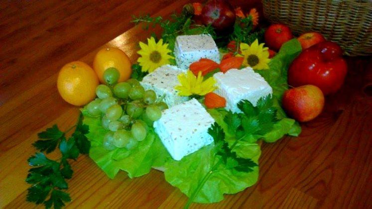 sery na desce przyozdobione kwiatami, obok owoce winogron