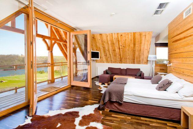 łóżko w pokoju, na podłodze skóra, otwarte okno z widokiem na zewnątrz