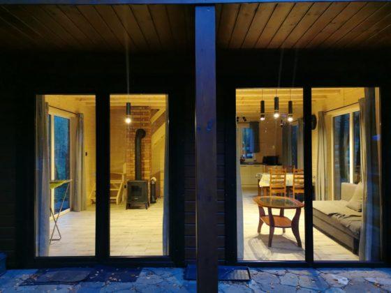 wnętrze domu widziane z zewnątrz, salon z kanapą i kominkiem