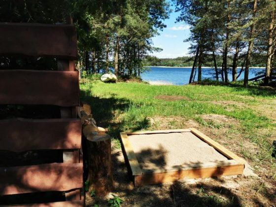 fragment domu, piaskownica i jezioro w niedalekiej odległości
