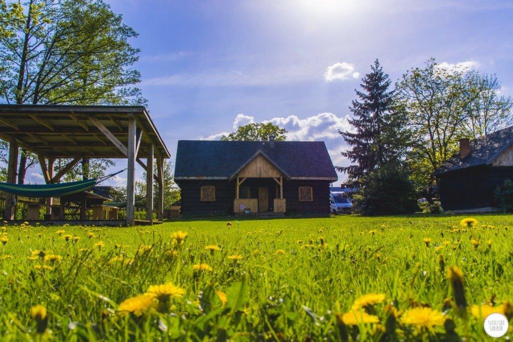 odnowiony stary dom na tle kwitnącej łąki