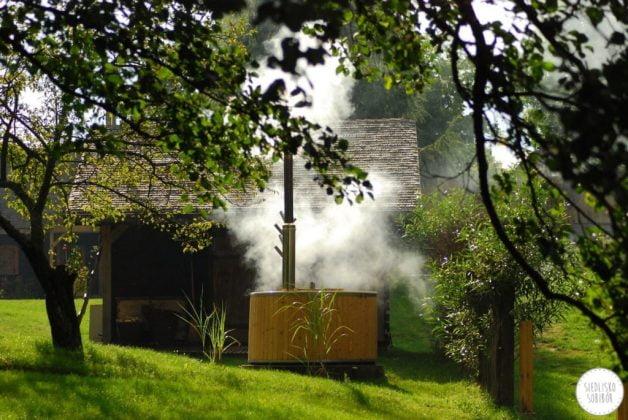dym unosi się z wypełnionej gorącą wodą drewnianej bali