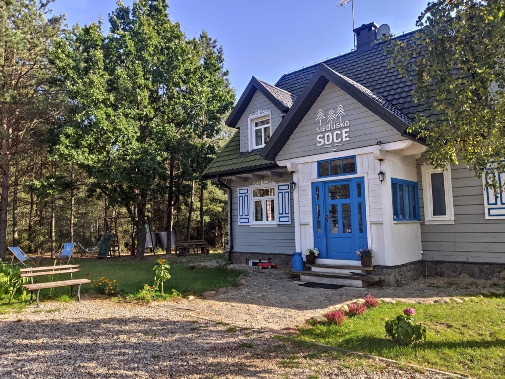 biało szary dom z kolorowymi obramowaniami okien i niebieskie drzwi do domu, dom w lesie